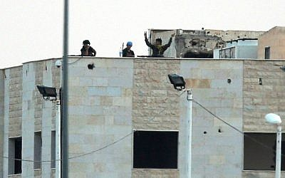 In this photo taken from the Turkish side of the border between Turkey and Syria, in Akcakale, southeastern Turkey, Kurdish fighters wave and flash the V-sign as the hold their positions atop pf a building in the outskirts of Tal Abyad, Syria, Monday, June 15, 2015 (AP Photo/Lefteris Pitarakis)