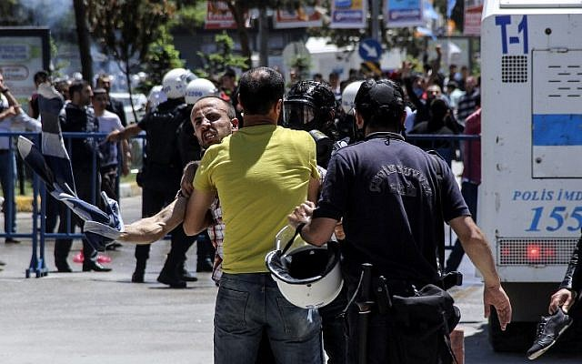 Turkish riot policemen grab a man during clashes  in Erzurum between Turkish nationalists and supporters of pro-Kurdish People's Democratic Party (HDP) on June 4, 2015. (AFP/Ihlas News Agency)