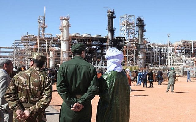 Algerian soldiers and officials stand in front of a gas plant in Ain Amenas where dozens were killed during a hostage taking, seen in background, during a visit organized by the Algerian authorities for news media, January 31, 2013. (AP, File)