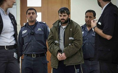 Police escort Yosef Haim Ben-David, one of the Jewish suspects in the murder of Muhammed Abu Khdeir, in the District Court in Jerusalem, on June 3, 2015. (Hadas Parush/Flash90)