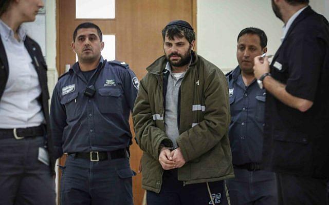 Police escort Yosef Haim Ben-David, one of the Jewish suspects in the murder of Muhammed Abu Khdeir, in the District Court in Jerusalem, on June 3, 2015. (Hadas Parush/Flash90)