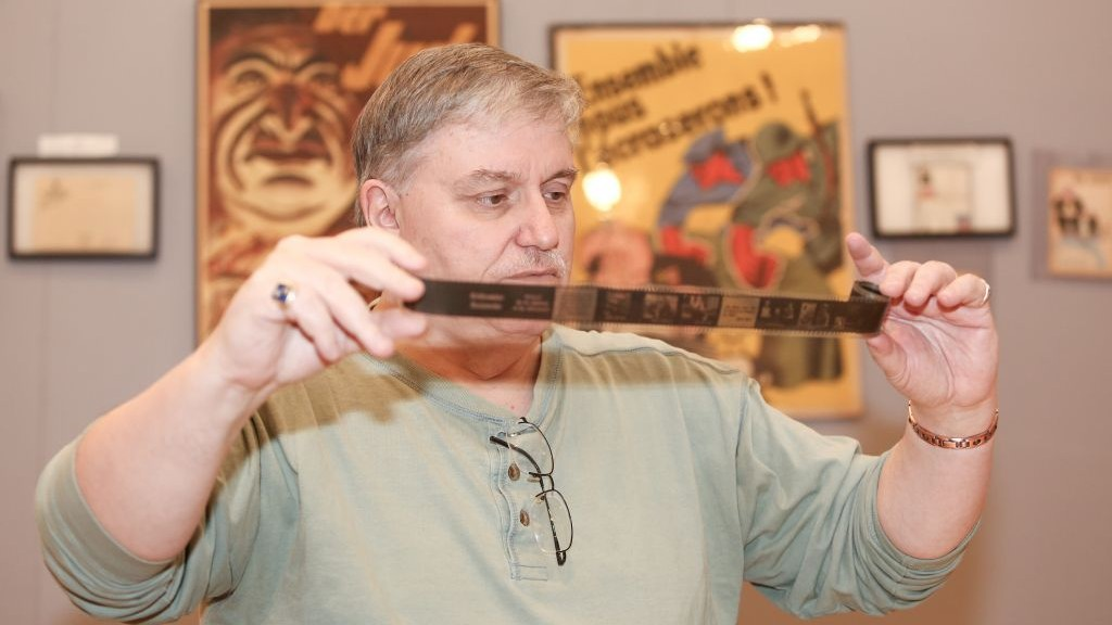 Darrell English, founder of the New England Holocaust Institute & Museum, has amassed 3,000 objects connected to the Shoah during 40 years of buying, selling and trading artifacts. Here, English examines an original Nazi propaganda filmstrip related to the 'T4' euthanasia program, one item in his Massachusetts-based collection. (photo credit: Elan Kawesch/The Times of Israel)