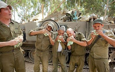 Illustrative photo: IDF reserve soldiers seen eating in a staging area near the border with Gaza in Southern Israel on July 20, 2014, during Israel's Operation Protective Edge. (Moshe Shai/Flash90)