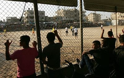 Palestinian youths watch a local football match, just before sunset, at a refugee camp in Rafah, in the southern Gaza Strip, July 14, 2013. (Abed Rahim Khatib/Flash 90)