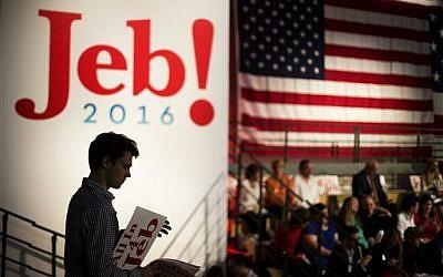 Campaign intern Jack Nalen hands out signs endorsing Jeb Bush at Miami Dade College in Miami, Monday, June 15, 2015 (AP Photo/David Goldman)