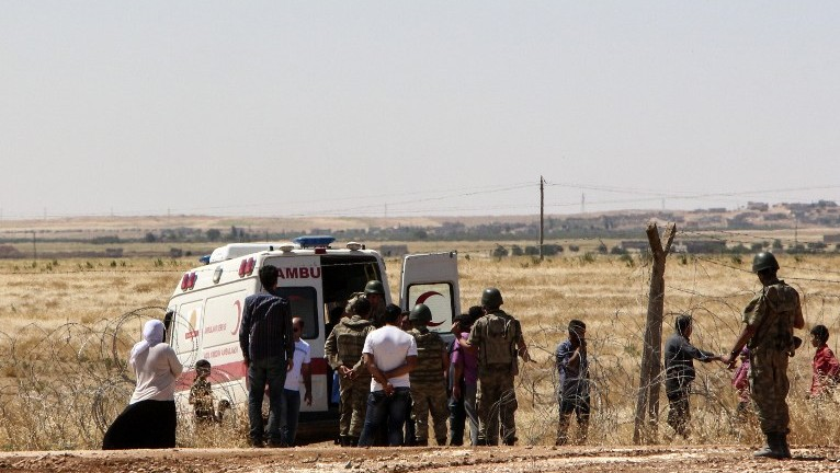 An ambulance waits in Suruc in Turkey's in Sanliurfa province to transport wounded people near the Syrian border town of Kobane on June 25, 2015. (AFP)
