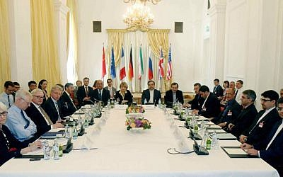 Delegates sit around a table prior to a bilateral meeting as part of the closed-door nuclear talks with Iran at a hotel in Vienna, Austria. (AP Photo/Ronald Zak, File)