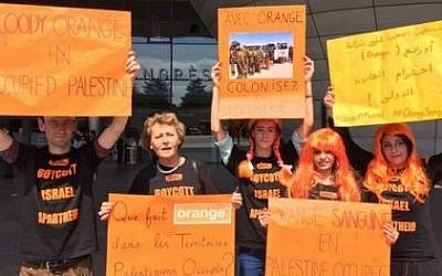 A photo by BDS France showing protesters calling on the cellular provider to cut ties with Israel. The signs say in French 'Blood red Orange in occupied Palestine,' 'What is Orange doing in the occupied Palestinian territories?' and 'Colonized and limited with Orange.' (Screen capture: Electronic Intifada)