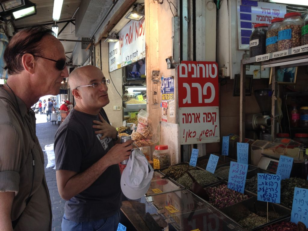 Jack Gottlieb (left) and Gil Hovav looking for herbs at Tel Aviv's Levinsky Market (Jessica Steinberg/Times of Israel)