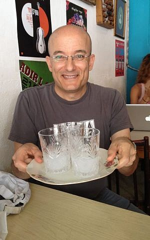 Gil Hovav serves up a mid-morning drink, arak distilled with water (Jessica Steinberg/Times of Israel)