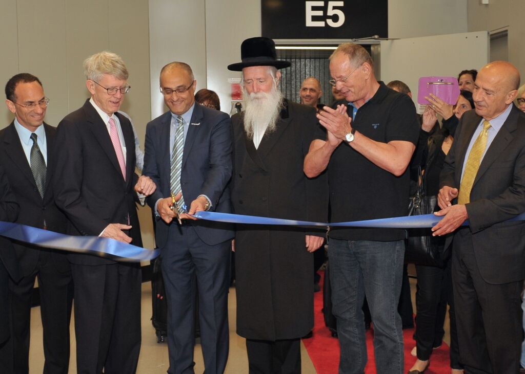 During a ceremony conducted at Boston's Logan International Airport on June 28, 2015, officials cut a ribbon outside the new Boston-TLV nonstop flight's boarding gate. Pictured (from left) are Israel's Consul-General to New England, Yehuda Yaakov; Chief Executive Officer of the Massachusetts Port Authority, Thomas Glynn; El Al CEO, David Maimon; Rabbi Yitvhal Dovid Grossman; El Al Chairman Amikam Cohen, and El Al Vice President and Project Manager, Boston route, Danny Saadon. (photo credit: Allan Dines/Massport)