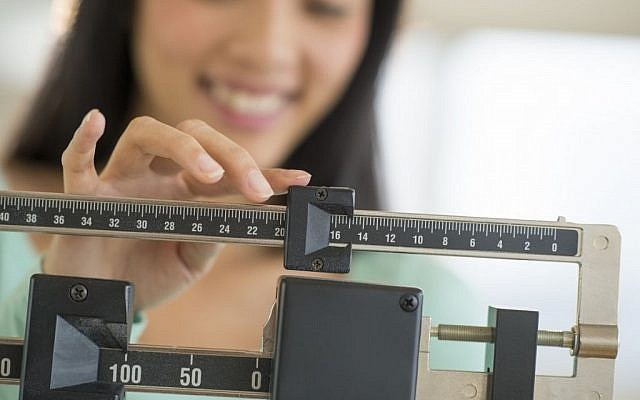 Illustrative photo of a woman on a scale. (Image via Shutterstock)