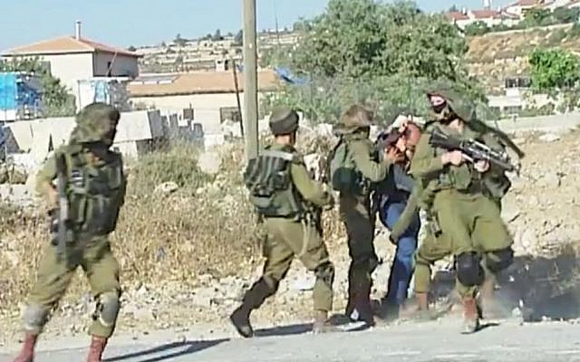 A Palestinian man is beaten and restrained by IDF soldiers during a violent demonstration in the Jelazoun refugee camp, near Ramallah, on June 12, 2015. (screen capture: Palestine TV)