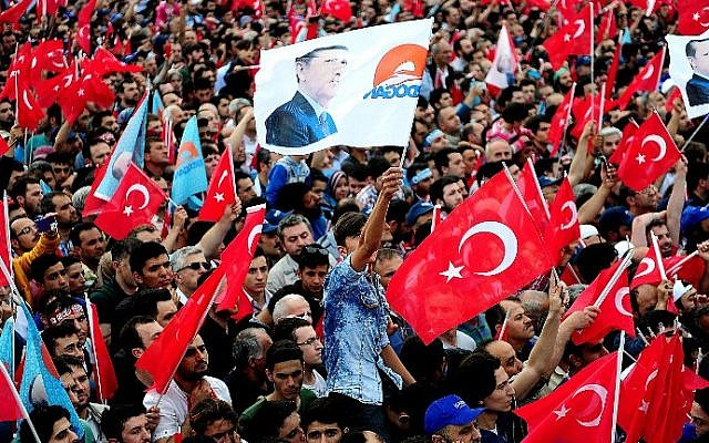 People wave Turkish flags, including one bearing the image of President Recep Tayyip Erdogan, on May 30, 2015, during a campaign rally. (AFP/Ozan Kose)