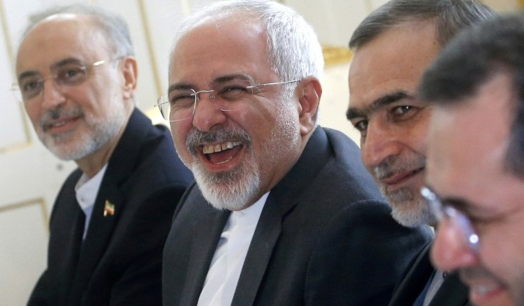 Iranian Foreign Minister Javad Zarif  (C) laughs at the start of a meeting on Iran's nuclear program with US Secretary of State John Kerry in Vienna, Austria, on June 30, 2015. (AFP PHOTO/POOL/CARLOS BARRIA)