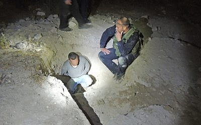 A man suspected of illegal excavation at an antiquities site in Jerusalem is shown handcuffed alongside inspectors, Wednesday, July 8, 2015 (Israel Antiquities Authority)
