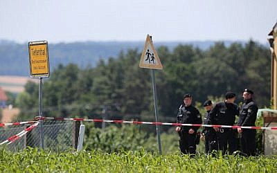 Policemen stand at a crime scene in Tiefenthal-Leutershausen near Ansbach, southern Germany, after a gunman in a car killed a woman and a cyclist in drive-by shootings on July 10, 2015. (AFP PHOTO / DPA / DANIEL KARMANN)