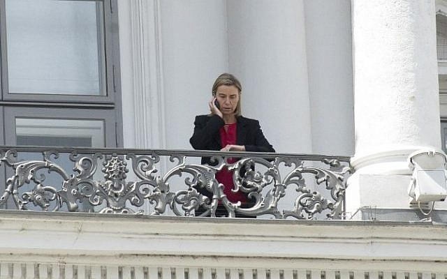 High Representative of the European Union for Foreign Affairs and Security Policy Federica Mogherini speaks on the phone from a balcony of the Palais Coburg Hotel where the Iran nuclear talks meetings are being held in Vienna, Austria on July 10, 2015. (Joe Klamar/AFP)