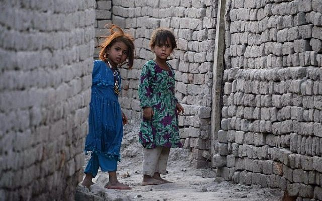 In this July 5, 2015 photo, Afghan girls who fled from Kot district of the eastern Nangarhar' province, following threats from the Islamic State group to leave their homes, look around a corner next to their temporary homes in Jalalabad. (AFP/ Noorullah Shirzada)