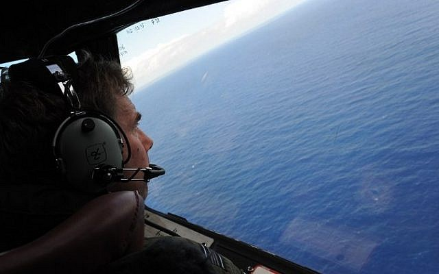 This file photo taken from a Royal New Zealand Air Force (RNZAF) P-3K2-Orion aircraft on April 13, 2014 shows co-pilot and squadron leader Brett McKenzie helping to look for objects during the search for missing Malaysia Airlines flight MH370, off Perth in Western Australia. (AFP/Pool/Greg Wood)
