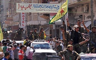 File: Kurdish People's Protection Units (YPG) fighters wave their movement's flag and cheer as they parade in the northeastern Syrian town of Qamishli after returning from battling Islamic State group jihadists in Tal Abyad on the border with Turkey, June 24, 2015. (AFP/Delil Souleiman)