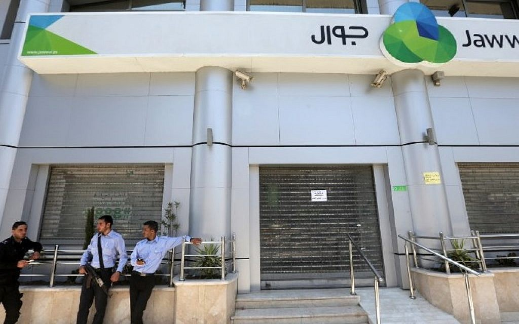 Hamas police stand guard in front of the Jawwal company's headquarters in Gaza City on June 30, 2015. (AFP/Mahmud Hams)