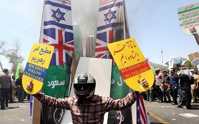An Iranian protester holds placards as he stands in front of prints of Israeli, US, British and Saudi Arabian flags during a demonstration to mark the Quds (Jerusalem) International day in Tehran on July 10, 2015. (AFP/ ATTA KENARE)