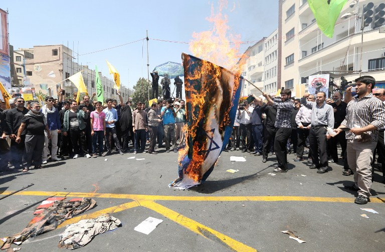 Iranian protesters burn an Israeli flag during a demonstration to mark al-Quds (Jerusalem) Day in Tehran on July 10, 2015. (AFP/ATTA KENARE)