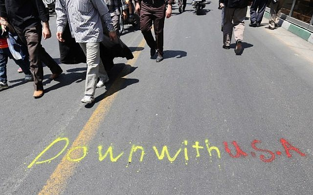 Iranians walk past a graffiti on a street during a demonstration to mark the Quds (Jerusalem) International day in Tehran on July 10, 2015. (AFP PHOTO / ATTA KENARE)