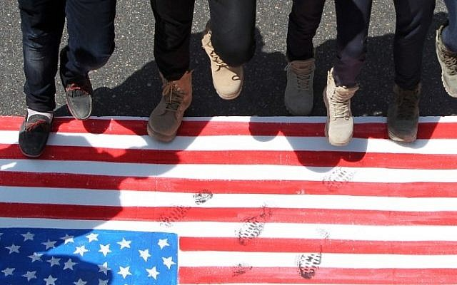 Iraqi men step on a US flag during a demonstration marking the Quds (Jerusalem) International day in the capital Baghdad, on July 10, 2015. (AFP/ AHMAD AL-RUBAYE)