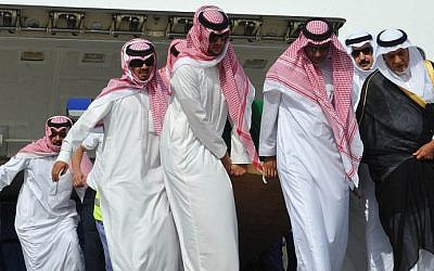Saudi Prince Turki al-Faisal (R) stands next to the coffin of Prince Saud al-Faisal as it is being unloaded from a plane upon its arrival in Jeddah on July 11, 2015, a few hours before the funeral ceremony held in the Muslim holy city of Mecca. (AFP PHOTO / STR)
