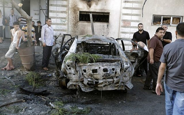 Palestinians gather around a burnt-out car in Gaza City on July 19, 2015, after explosions destroyed five cars in Gaza belonging to members of Hamas and Islamic Jihad, witnesses and a security source said, amid tensions between the Palestinian territory's rulers and Islamist extremists. (AFP/MOHAMMED ABED)
