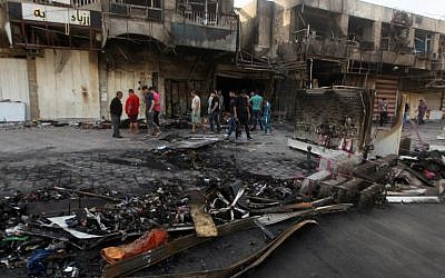 Iraqi men gather outside a burnt shop in Baghdad on July 22, 2015 following two late night car bombs which killed at least 19 people in mostly Shiite neighborhoods of the Iraqi capital, according to police. (AFP PHOTO/ AHMAD AL-RUBAYE)