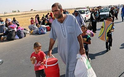Displaced Iraqis carry their belongings on July 22, 2015 at a gathering point in the northern city of Kirkuk. (AFP / MARWAN IBRAHIM)