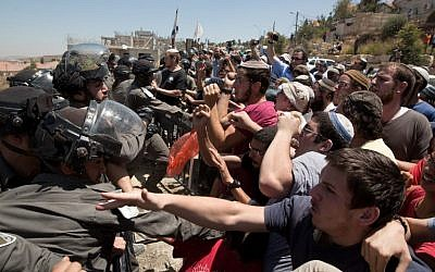 Israeli settlers scuffle with security forces as demolition starts of the Dreinoff buildings in the settlement of Beit El, in the West Bank, on 29 July, 2015. (AFP PHOTO / MENAHEM KAHANA)