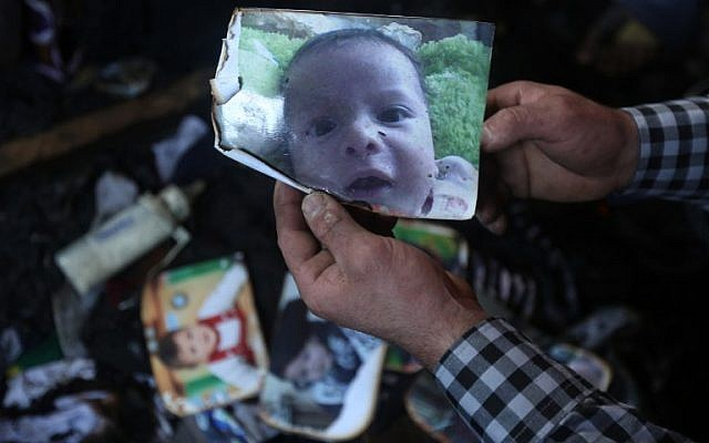 A man shows a picture of 18-month-old Palestinian toddler Ali Saad Dawabsha, who died when his family house was set on fire by alleged Jewish extremists in the West Bank village of Duma, on July 31, 2015. (AFP/Jaafar Ashtiyeh)