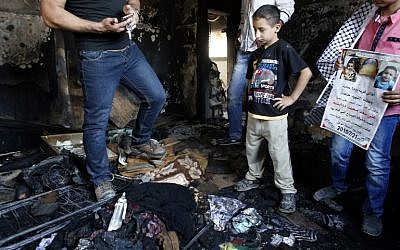Palestinians inspect the damage as they stand in a house in the West Bank village of Duma set on fire in an apparent attack by Jewish terrorists, which killed 18-month-old Palestinian toddler Ali Saad Dawabsha on July 31, 2015. (AFP PHOTO/THOMAS COEX)
