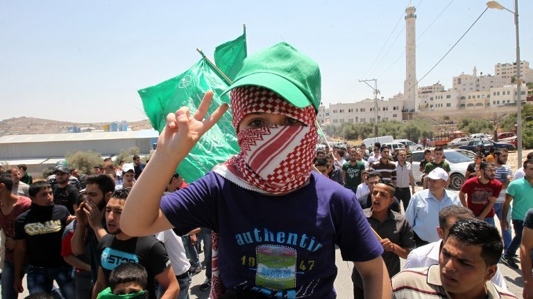 A child flashes the sign of victory during a demonstration of Palestinian Islamist Hamas supporters in support of Jerusalem's Al-Aqsa mosque on July 31, 2015 in the Israeli-controlled area called H2, in the West Bank town of Hebron. (Hazem Bader/AFP)