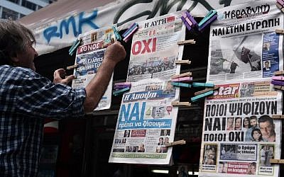 "A newsagent hangs newpapers bearing ""No"" and ""Yes"" headlines in central Athens, on July 4, 2015, on the eve of the Greek referendum on its bailout terms. (AFP/ LOUISA GOULIAMAKI)"
