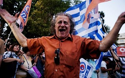 A man celebrates at Klafthmonos Square in Athens on July 5, 2015 after the first exit-polls of the Greek referendum. (AFP/IAKOVOS HATZISTAROU)