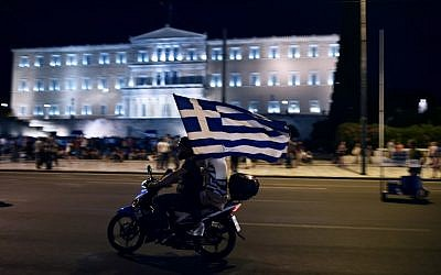 A motorcyclist with his passenger holding a Greek flag passes in front of the Greek Parliament in Athens on July 5, 2015, after early results showed those who rejected further austerity measures in a crucial bailout referendum were poised to win. (AFP/ARIS MESSINIS)