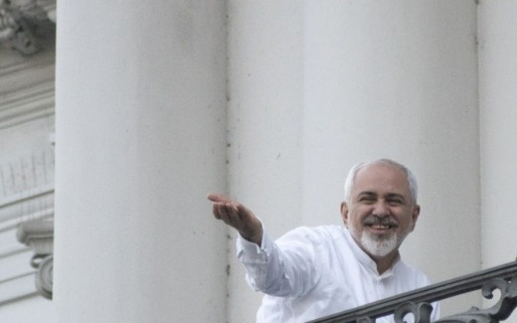 Iranian Foreign Minister Mohammad Javad Zarif gestures toward reporters as he talks with Iranian Deputy Foreign Minister, Iranian deputy foreign minister for European and American Affairs, and the brother of the Iranian president (not pictured) onto a balcony of the Palais Coburg Hotel, where the Iran nuclear talks meetings are being held in Vienna on July 11, 2015 (AFP PHOTO / JOE KLAMAR)