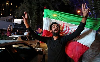 An Iranian man flashes the victory sign as an other holds the Iranian national flag during celebration in northern Tehran on July 14, 2015, after Iran's nuclear negotiating team struck a deal with world powers in Vienna. (AFP PHOTO/ATTA KENARE)