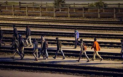 Migrants walk along railway tracks at the Eurotunnel terminal on July 28, 2015 in Calais-Frethun. (AFP PHOTO / PHILIPPE HUGUEN)