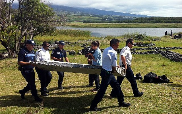 Police carry a piece of debris from an unidentified aircraft found in the coastal area of Saint-Andre de la Reunion, in the east of the French Indian Ocean island of La Reunion, July 29, 2015.  (AFP/YANNICK PITOU)