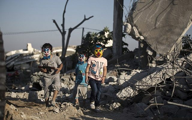 Palestinian children play in the rubble of buildings, reportedly destroyed during the 50-day war between Israel and Hamas terrorists in the summer of 2014, in Gaza City on July 21, 2015. (AFP / MOHAMMED ABED)