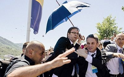 Bodyguards try to protect Serbian Prime Minister Aleksandar Vucic (C) from stones hurled at him by an angry crowd at the Potocari Memorial Center, near the eastern Bosnian town of Srebrenica on July 11, 2015. (AFP PHOTO / DIMITAR DILKOFF)
