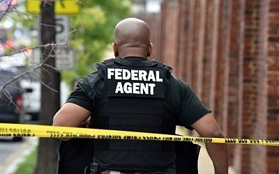 A federal agent patrols near the scene of an unconfirmed shooting at the Navy Yard in Washington, DC on July 2, 2015. (AFP PHOTO/ MLADEN ANTONOV)