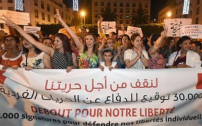 Moroccans shout slogans and hold placards during a demonstration in Rabat against the arrest of two Moroccan women after their dresses were deemed too tight, July 6, 2015. (AFP/FADEL SENNA)