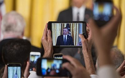 Guests photograph US President Barack Obama as he speaks during a reception for the 25th anniversary of the Americans with Disabilities Act (ADA) in the East Room of the White House in Washington, DC, July 20, 2015 (AFP PHOTO / SAUL LOEB)